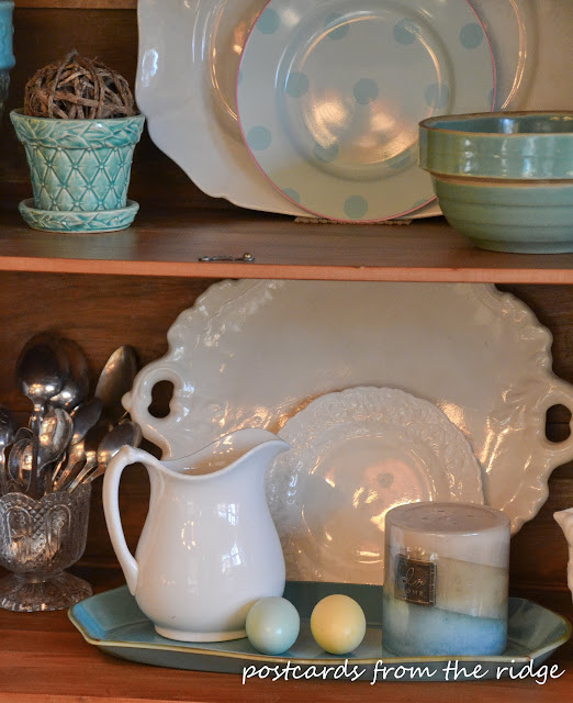 Pretty display of ironstone, vintage silver, and pottery with touches of turquoise