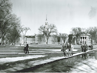 A photograph of men on The Dartmouth campus, walking along boards to avoid standing water.