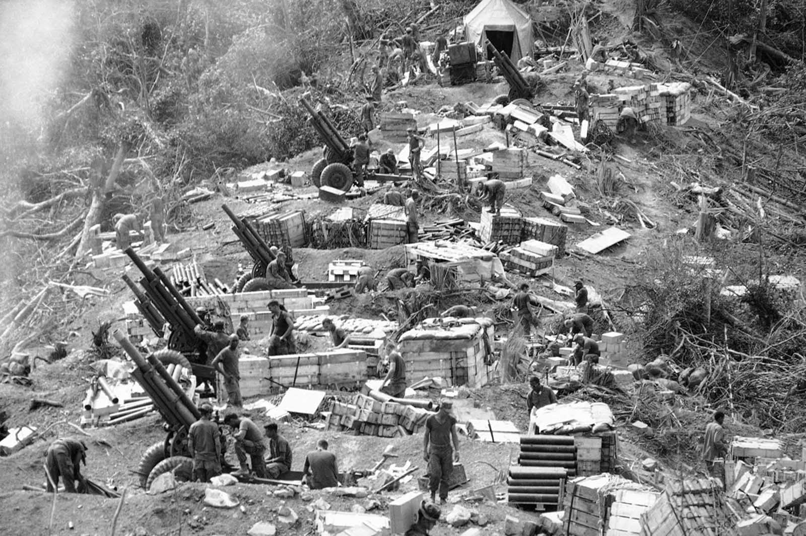 Marines prepare their 105-mm Howitzers for action at the end of a day in which this dense jungle area west of Hue was chopped down and molded into a fire-support base for a sweep of the area on February 18, 1969. Troops used explosives and earth-moving equipment to carve out the gun pits and bunkers which by nightfall became a fire-support base.