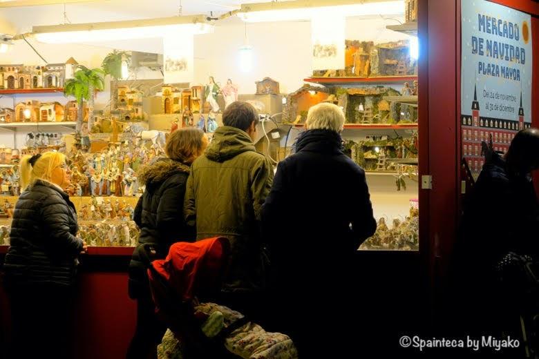 マドリードのマヨール広場のクリスマスマーケットでベレン人形を買う家族