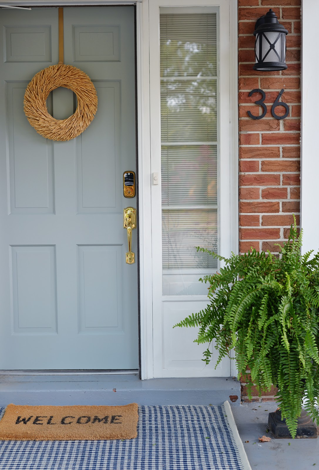 fresh traditional front porch decor with blue grey painted front door and layered Annie Selke rugs