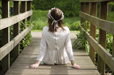 Niña vestida para una boda sentada en un puente