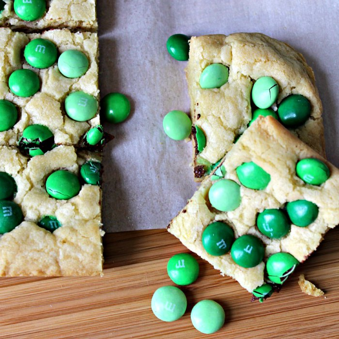 Mint M & M Sugar Cookie Bars on a board, cut into squares studded with green mint M&Ms