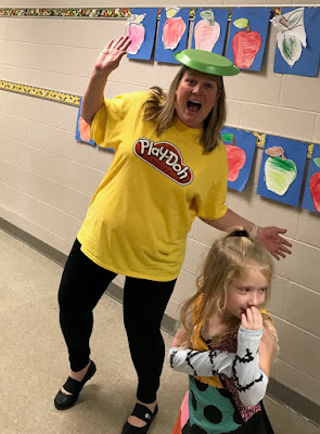 Teacher wearing a Play Doh shirt with a girl standing next to her with her hand on her mouth
