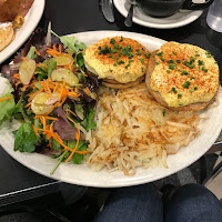 Two English muffins covered in a yellow sauce with salad and a pile of fried grated potato.