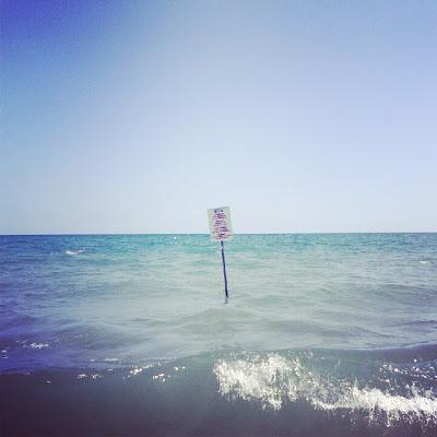 Fotografia con smartphone di cartello di limite acque sicure al mare