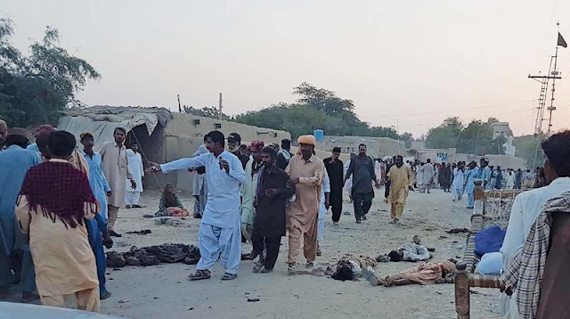 Image Attribute: Devotees gather around the bodies of blast victims after a suicide bombing near a Sufi shrine in the Gandawa area of Jhal Magsi district of Balochistan on October 5, 2017. / Source: AFP / WARNING: Viewer Discretion Advised