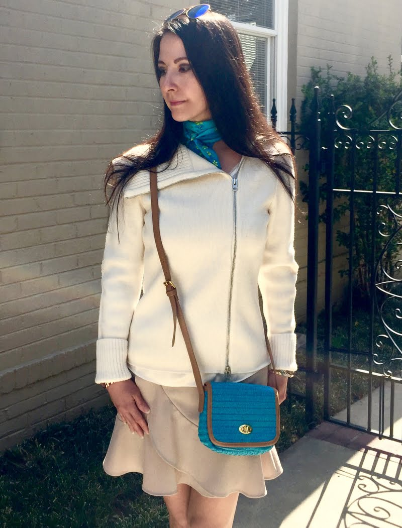 Top half of body wearing a beige zip up sweater, blue scarf tied around neck, and blue cross body bag.