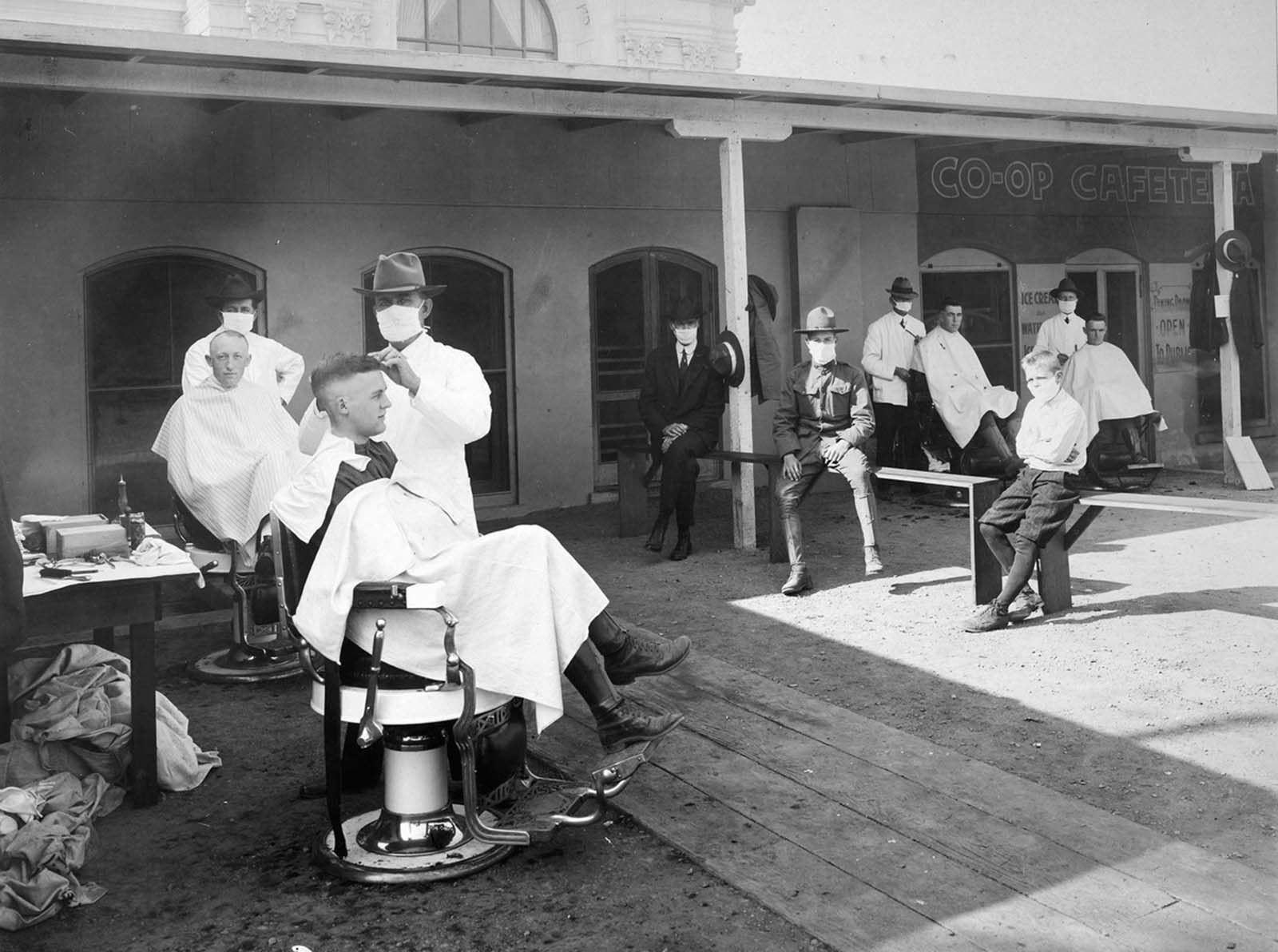 An open-air barber shop serves customers during the epidemic at the University of California, Berkeley, 1919.