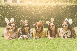 Cinco mujeres jóvenes y amigas tumbadas en el césped en un día soleado, todas mirando a la cámara con gafas de sol.