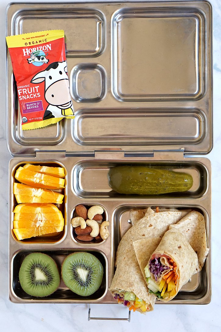 Colorful lunch box packed with a rainbow veggie tortilla wrap.
