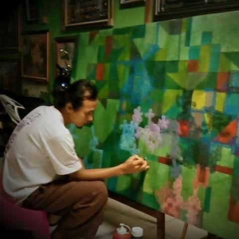 Omen saat menuangkan warna di atas kanvas.