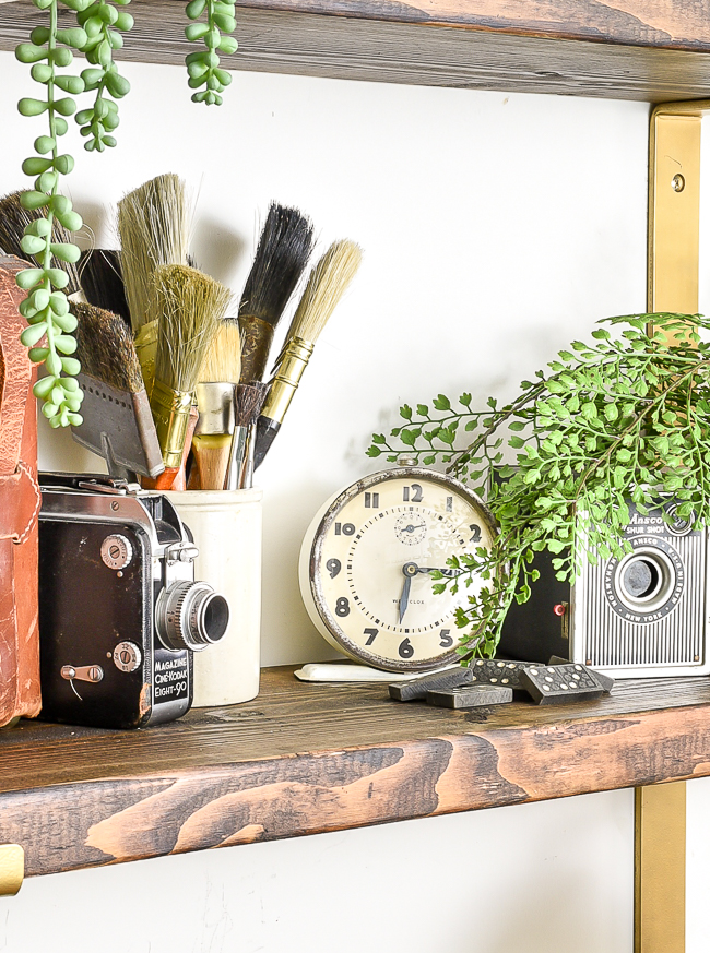 Vintage clock, cameras and paint brushes styled on wood shelves
