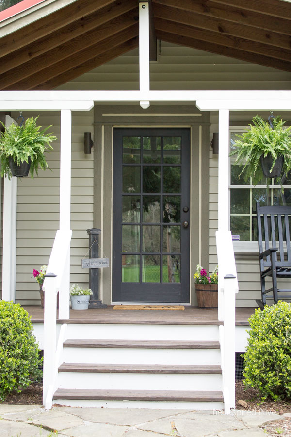 How to refinish your old wood front porch. We used Behr Cordovan Brown and Pinto White stains. The HomeRight Paint Stick helped us update our farmhouse front porch the easy way!