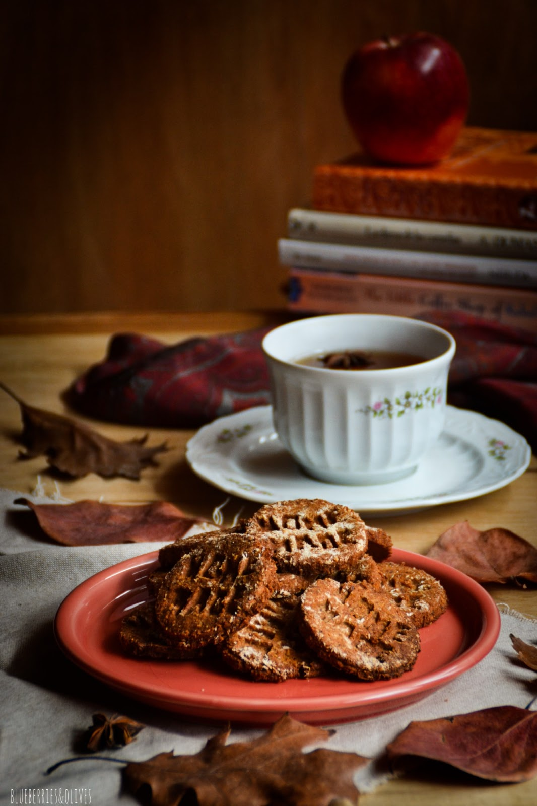 Piled cookies on red ceramic dish, dry autumn leaves, dark background, old wood, piles books with red apple on top