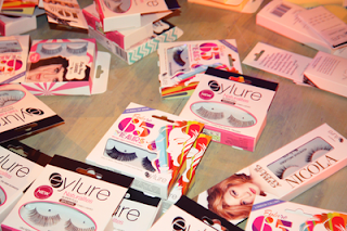 lots of eylure false lashes in their packaging on a wooden table