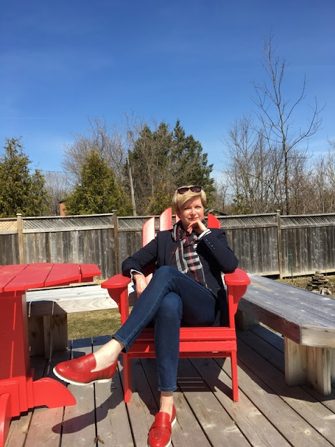 woman in navy jacket, jeans, and red loafers sitting in a red Adirondack chair