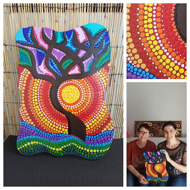 Hier wird ein farbenfrohes Bild gezeit, welches von der Künstlerin Elke Wolf erstellt wurde. Auf dem Bild ist ein Baum zu sehen und hinter ihm leichtet die Sonne. Das Bild besteht fast gänzlich aus Punkten. Es handelt sich hier um Punktmalerei. Auf einem kleineren bild sind Elke Wolf und Anna Pianka zu sehen, wie sie das Bild halten.