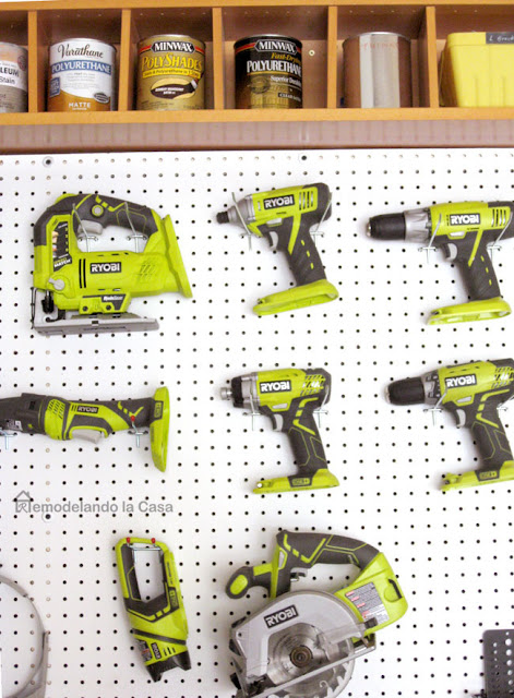 White pegboard on the wall with Ryobi tools on it.