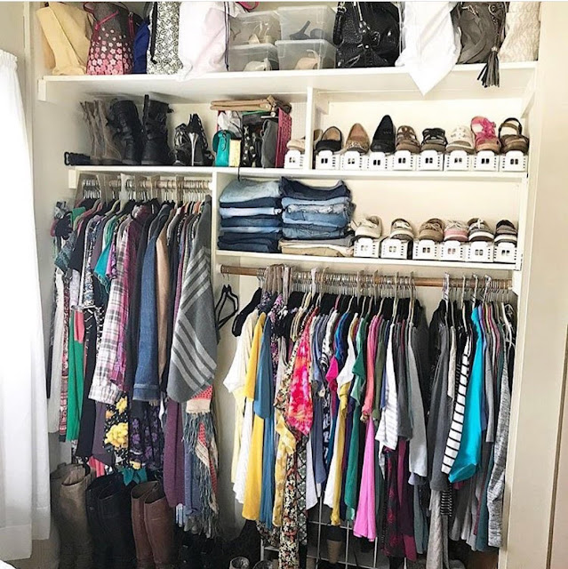 A closet organized by type with shoes and handbags