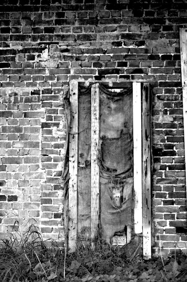 Blog + Fotografie by it's me!   fim.works | SchwarzWeissBlick No 13 | leerstehendes Backsteinhaus | mit Säcken und Latten verammelte Tür