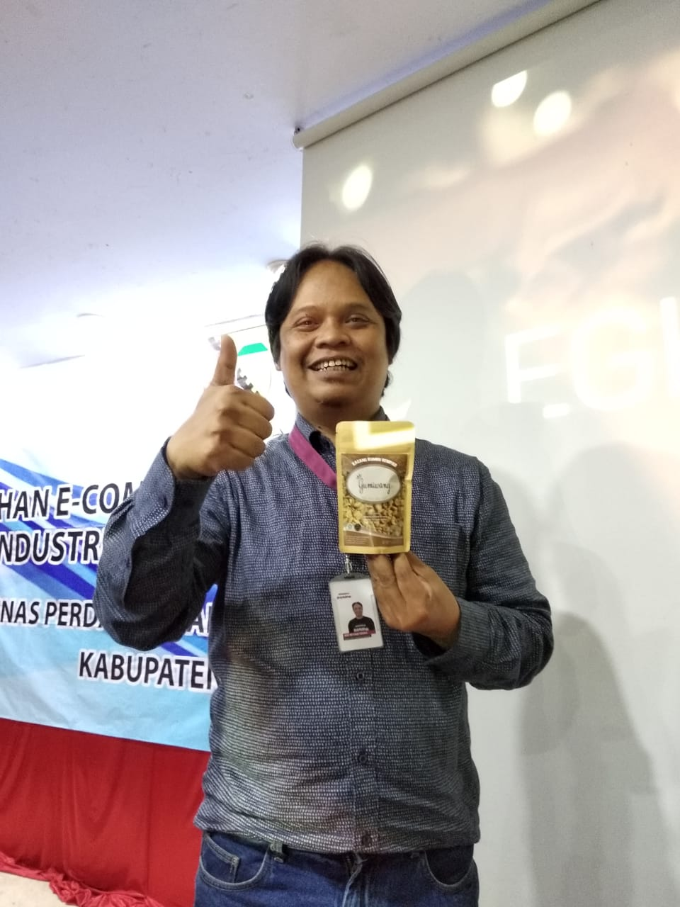 adetruna memegang produk cemilan ukm kabupaten bandung kacang bawang gumiwang