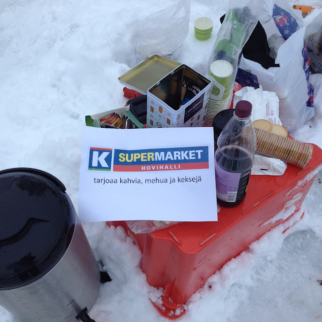 """""""K-supermarket Hovihalli tarjoaa kahvia, mehua ja keksejä"""" -lappu eväiden päällä lumessa"""
