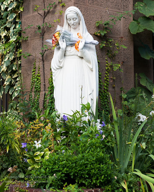 a photo of a statue of The Virgin Mary with Flowers in New York City