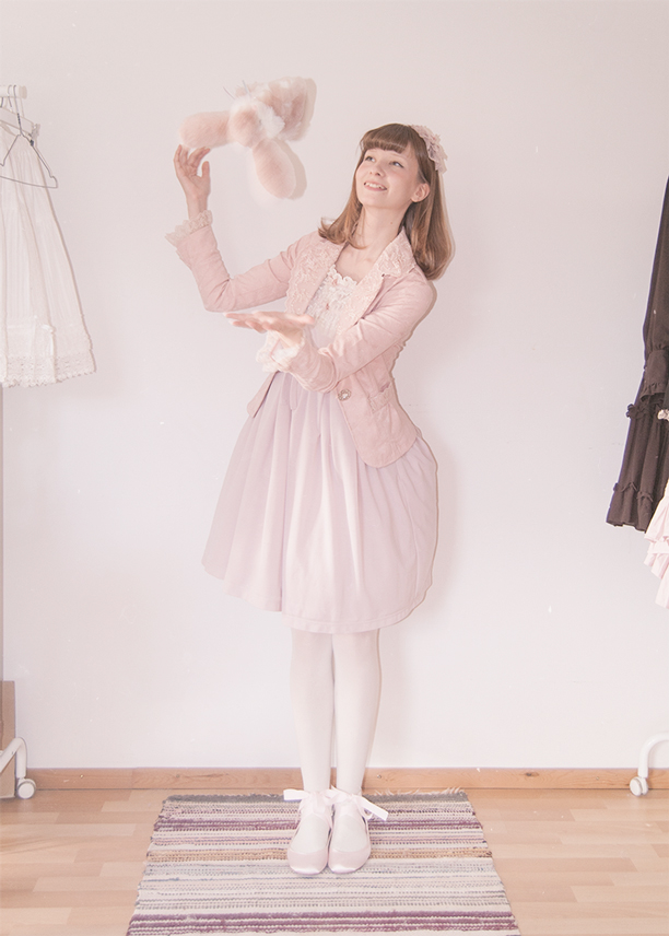 a girl dressed in a pink innocent world lolita dress throwing a bunny plushie