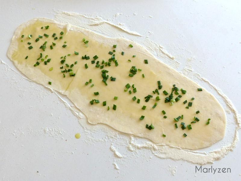 Badigeonnez légèrement d'huile d'olive à l'aide d'un pinceau et dispersez la ciboule ciselée.