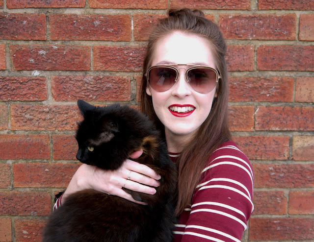 I'm standing in front of a red brick wall, smiling at the camera, and holding my black fluffy cat. I'm wearing sunglasses, red lipstick, and a burgundy stripy top.