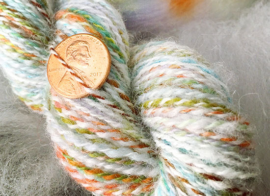 Skein of colorful handspun wool and alpaca yarn with a penny tucked in to show scale.