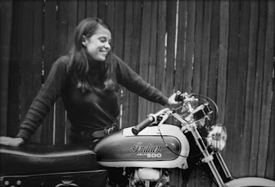 Woman admires a Velocette Indian motorcycle.
