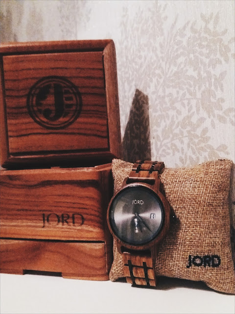 wooden watch wrapped around a hessian cushion with the display box behind it