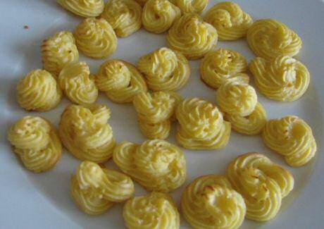 Lekkere, stevige hertoginnenaardappelen van aardappelpuree gespoten in toefjes en gebakken in de oven