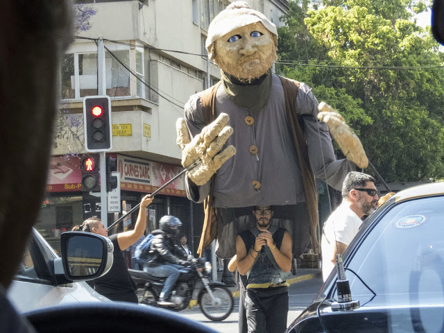 Why visit Santiago: Giant puppet performing at an intersection