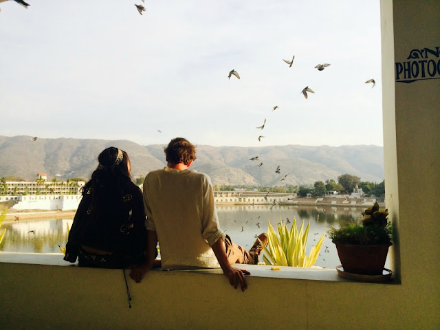 Girl and a friend sitting by the lake in Pushkar India