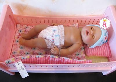 Пупс спит в кукольной кроватке