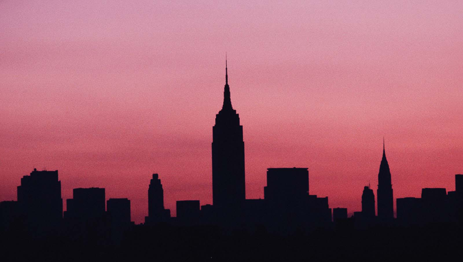 The sun rises on the darkened Manhattan skyline during a citywide blackout. 1977.