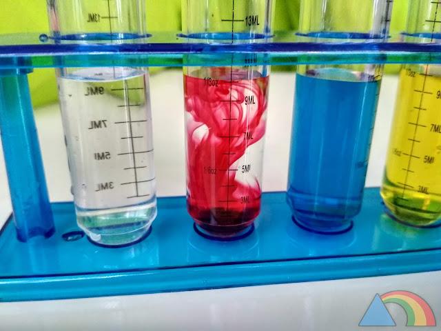 Colorante rojo disolviéndose en tubo de ensayo con agua