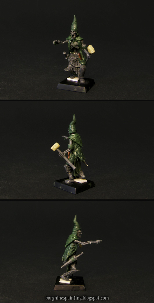 An unpainted, kitbashed Necrotect miniature made to fit in a Vampire Counts collection - wearing a pointy hat and holding a hammer.