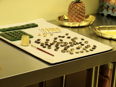 Making chocolate buttons in the mould of uniform buttons   in the kitchen display in a Royal Welcome  2015 exhibition at Buckingham Palace  Photo © Andrew Knowles