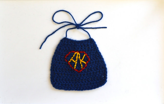 A deep blue crocheted cape with 'string' ties, all made with 8 ply acrylic yarn. The yellow initials 'A.K.' are embroidered in the centre of a red outlined 5-sided shape similar to an inverted triangle with the top corners cut off at an angle and the main point pointing downwards.