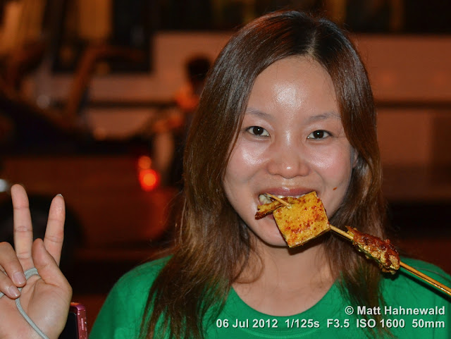 China, Beijing, Donghuamen night market, Chinese food delicacies, portrait, Chinese woman eating spicy fried tofu