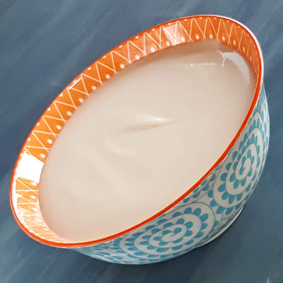 Bowl of creamy cauliflower soup on blue background