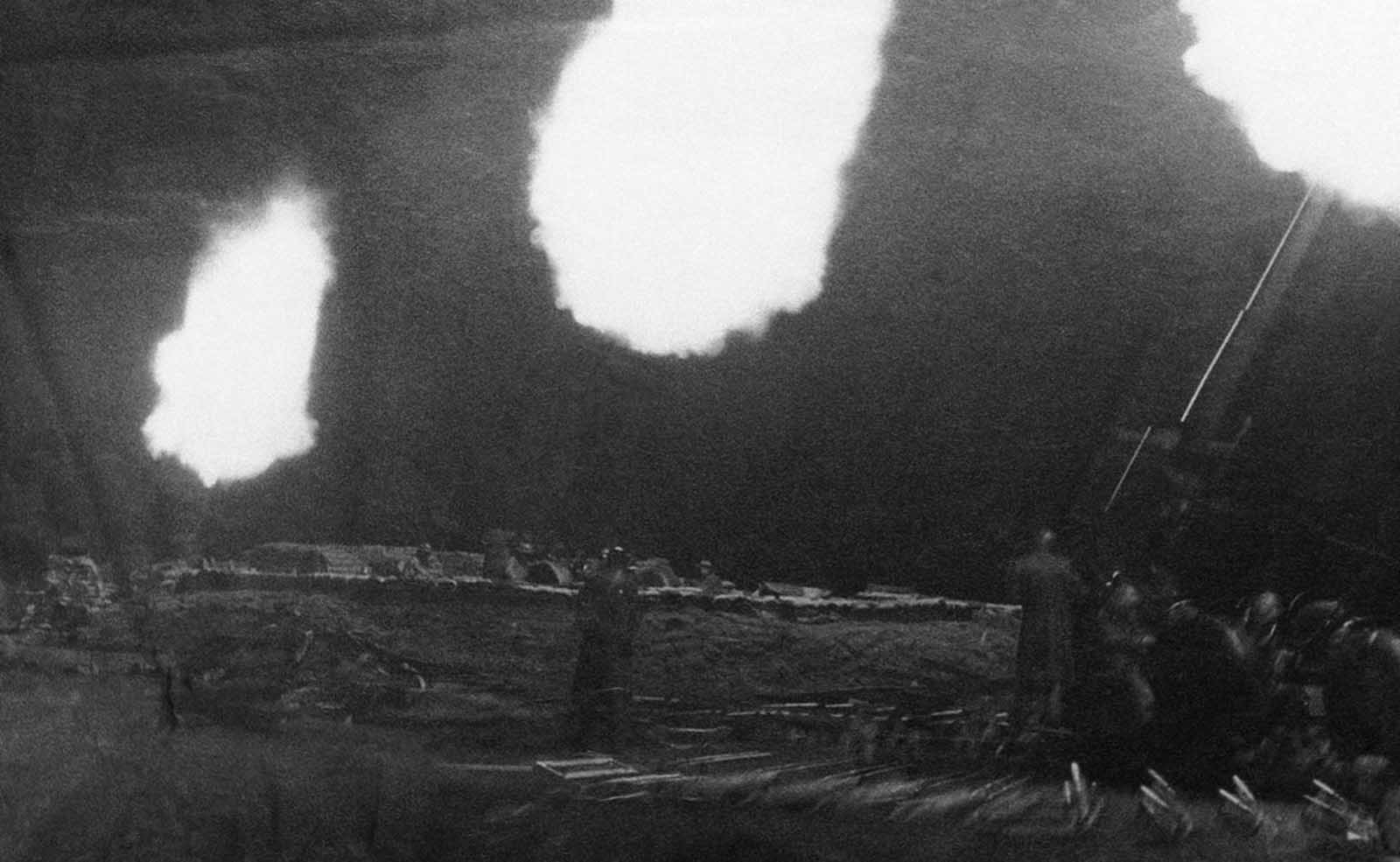 Three anti-aircraft guns flash in the dark in London, on September 20, 1940, throwing shells at raiding German planes. Shells in stacked rows behind the guns leap about as the concussions from the firing loosen them.