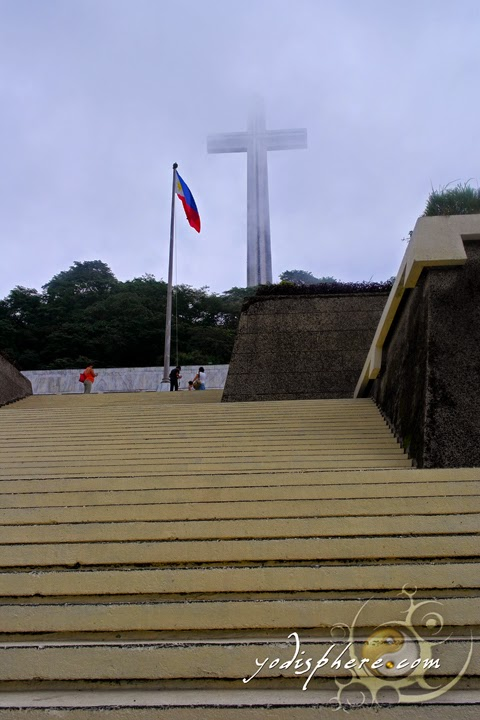 Philippine Flag waving against the towering Cross