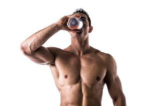 Hombre musculoso sin camiseta bebiendo un batido de proteínas