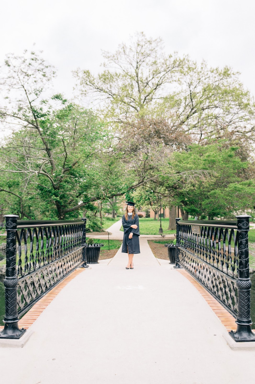 Graduate on the end of a bridge with trees framing the shot.