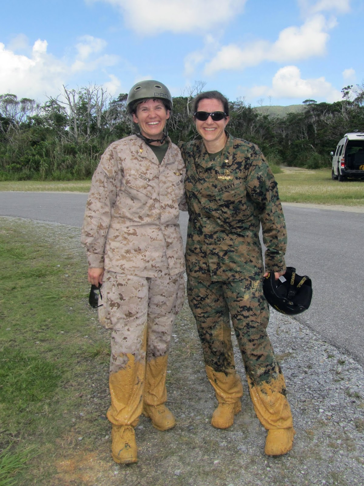 Two women in military uniform with mud up to their knees pose for a photo